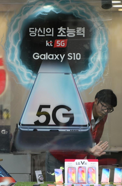 Un empleado prepara un anuncio para el servicio de redes móviles 5G de KT en una tienda de telecomunicaciones en Seúl el 4 de abril de 2019. (AFP)