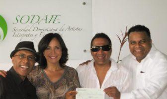 Momentos en que los ejecutivos de SODAIE, Pochy Familia y Ramón Orlando Valoy entregan los cheques que corresponden a Kinito Méndez y Adalgisa Pantaleón.