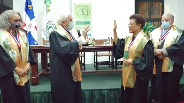 El presidente de la Academia de Ciencias, Luis Scheker Ortiz, juramenta a la educadora Dinorah García Romero. Observan Radhamés Mejía, coordinador de la Comisión de Educación y Olga Basora, miembro.